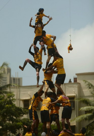 FILE - This file photograph taken on August 29, 2013, shows Indian Hindu devotees collapsing as they try to form a human pyramid to break the dahi-handi, curd-pot, suspended in the air during celebrations of Janmashtami, which marks the birth of Hindu God Lord Krishna, in Mumbai. India's top court on August 17, 2016, has banned children from taking part in a popular but potentially dangerous religious festival in the country's west that sees young boys scale human pyramids. The Supreme Court barred children aged under 18 from scaling the pyramids and restricted their height to 20 feet (six metres) following a string of accidents in recent years. (Punit Paranjpe/AFP/Getty Images)