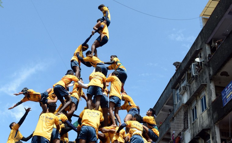 FILE - This file photograph taken on September 6, 2015 shows a Indian Hindu devotee (bottom L) falling during an attempt to form a human pyramid in a bid to reach and break a dahi-handi (curd-pot) suspended in the air during celebrations for the Janmashtami festival, which marks the birth of Hindu God Lord Krishna in Mumbai. India's top court on August 17, 2016, has banned children from taking part in a popular but potentially dangerous religious festival in the country's west that sees young boys scale human pyramids. The Supreme Court barred children aged under 18 from scaling the pyramids and restricted their height to 20 feet (six metres) following a string of accidents in recent years. (Indranil Mukherjee/AFP/Getty Images)