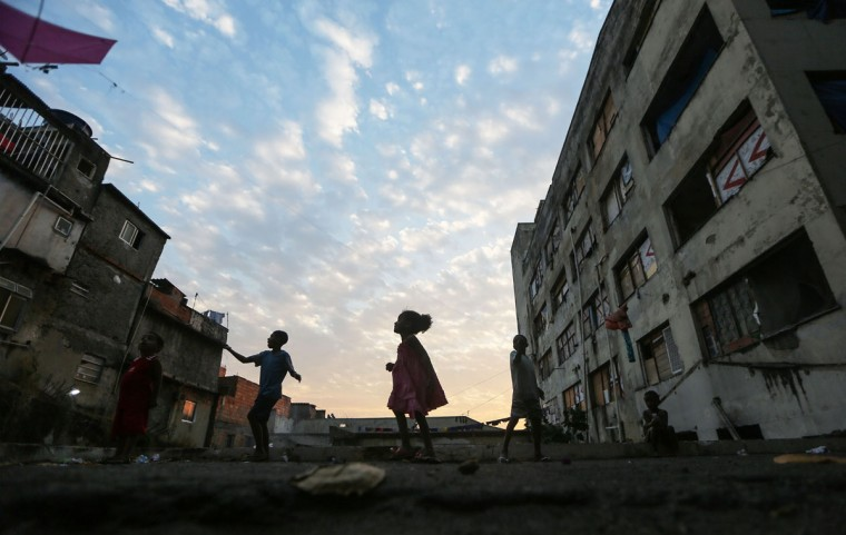 RIO DE JANEIRO, BRAZIL - AUGUST 09: Youngsters fly kids outside an occupied building in the Mangueira 'favela' community on August 9, 2016 in Rio de Janeiro, Brazil. Hundreds of residents who live in the surrounding structures must collect water from hoses as there is no running water in the buildings. Much of the Mangueira 'favela' community sits about a kilometer away from Maracana stadium, the site of the opening and closing ceremonies for the Rio 2016 Olympic Games. The stadium has received hundreds of millions of dollars in renovations ahead of the World Cup and Olympics. The Morar Carioca plan to urbanize Rio's favelas, or unplanned settlements, by 2020, was one key social legacy project heralded ahead of the Rio 2016 Olympic Games. The plan has mostly failed to materialize. Around 1.4 million residents, or approximately 22 percent of Rio's population, reside in favelas which often lack proper sanitation, health care, education and security due to gang and police violence. (Photo by Mario Tama/Getty Images)