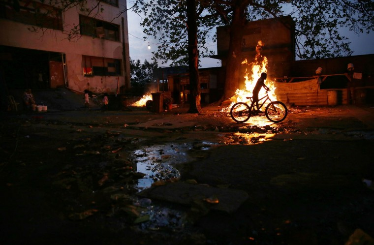 RIO DE JANEIRO, BRAZIL - AUGUST 09: A boy rides a bike past a trash fire outside an occupied building in the Mangueira 'favela' community on August 9, 2016 in Rio de Janeiro, Brazil. Hundreds of residents who live in the surrounding structures must collect water from hoses as there is no running water in the buildings. Residents often must burn trash due to a lack of public services. Much of the Mangueira 'favela' community sits about a kilometer away from Maracana stadium, the site of the opening and closing ceremonies for the Rio 2016 Olympic Games. The stadium has received hundreds of millions of dollars in renovations ahead of the World Cup and Olympics. The Morar Carioca plan to urbanize Rio's favelas, or unplanned settlements, by 2020, was one key social legacy project heralded ahead of the Rio 2016 Olympic Games. The plan has mostly failed to materialize. Around 1.4 million residents, or approximately 22 percent of Rio's population, reside in favelas which often lack proper sanitation, health care, education and security due to gang and police violence. (Photo by Mario Tama/Getty Images)