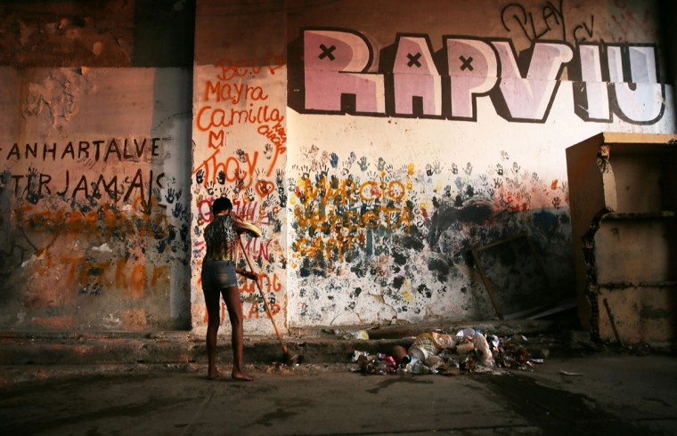 RIO DE JANEIRO, BRAZIL - AUGUST 09: A woman sweeps outside an occupied building in the Mangueira 'favela' community on August 9, 2016 in Rio de Janeiro, Brazil. Hundreds of residents who live in the surrounding structures must collect water from hoses as there is no running water in the buildings. Much of the Mangueira 'favela' community sits about a kilometer away from Maracana stadium, the site of the opening and closing ceremonies for the Rio 2016 Olympic Games. The stadium has received hundreds of millions of dollars in renovations ahead of the World Cup and Olympics. The Morar Carioca plan to urbanize Rio's favelas, or unplanned settlements, by 2020, was one key social legacy project heralded ahead of the Rio 2016 Olympic Games. The plan has mostly failed to materialize. Around 1.4 million residents, or approximately 22 percent of Rio's population, reside in favelas which often lack proper sanitation, health care, education and security due to gang and police violence. (Photo by Mario Tama/Getty Images)