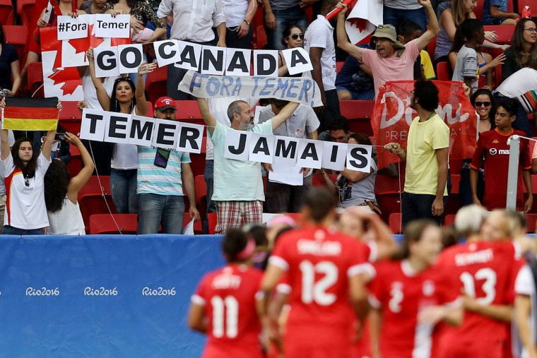 BRASILIA, BRAZIL - AUGUST 09: Protesters hold banners against the interim president of Brazil Michel Temer during the Women's First Round Group F match between Germany and Canada on Day 4 of the Rio 2016 Olympic Games at Mane Garrincha Stadium on August 9, 2016 in Brasilia, Brazil. (Photo by Celso Junior/Getty Images)