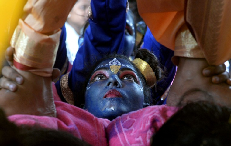 An Indian participant dressed as the Hindu god Lord Krishna helps support others making a 'human pyramid' during a cultural event in the run up to the dahi handi (curd pot) celebrations of 'Janmashtami', which mark the birth of Lord Krishna, in Mumbai on August 23, 2016. India's top court on August 17, 2016, has banned children from taking part in a popular but potentially dangerous religious festival in the country's west that sees young boys scale human pyramids. The Supreme Court barred children aged under 18 from scaling the pyramids and restricted their height to 20 feet (six metres) following a string of accidents in recent years. (Indranil Mukherjee/AFP/Getty Images)