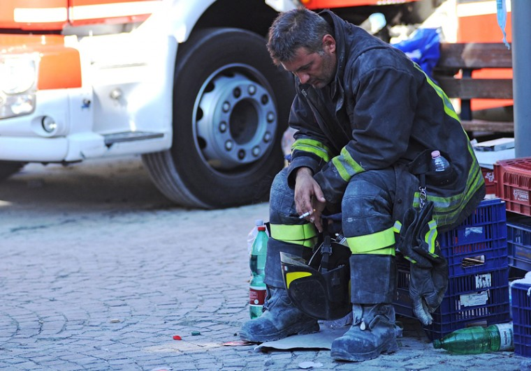 A firefighter takes a rest in the central Italian village of Amatrice on Wednesday after a powerful earthquake rocked central Italy. The powerful pre-dawn earthquake devastated mountain villages in central Italy, leaving at least 73 people dead, dozens more injured or trapped under the rubble and thousands temporarily homeless. Scores of buildings were reduced to dusty piles of masonry in communities close to the epicenter of the pre-dawn quake. (MARCO ZEPPETELLA/AFP/Getty Images )