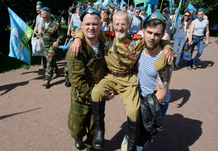 Former Russian soldiers of the airborne forces carry a man wearing WW II military uniform as they celebrate Paratroopers' Day in central Saint Petersburg on August 2, 2016. (Olga Maltseva/AFP/Getty Images)