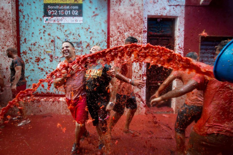 """Revelers covered in tomato pulp participate in the annual """"tomatina"""" festivities in the village of Bunol, near Valencia on Wednesday. (BIEL ALINO/AFP/Getty Images)"""