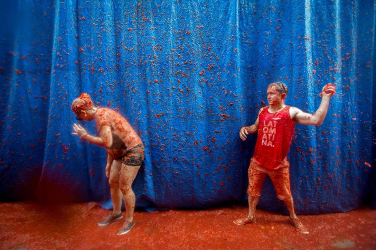 "Revelers covered in tomato pulp participate in the annual ""tomatina"" festivities in the village of Bunol, near Valencia. on Wednesday. (BIEL ALINO/AFP/Getty Images)"