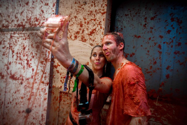 "Revelers covered in tomato pulp take a selfie in the annual ""tomatina"" festivities in the village of Bunol, near Valencia on Wednesday. (BIEL ALINO/AFP/Getty Images)"