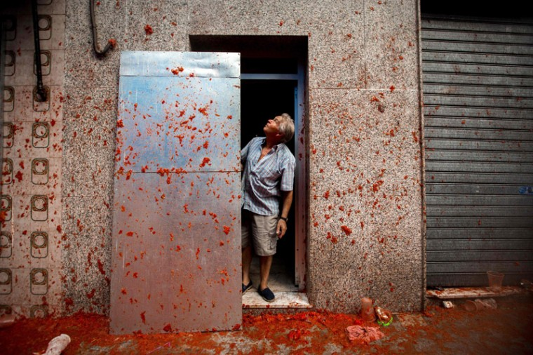 "A resident looks at a wall pelted with tomato pulp during the annual ""tomatina"" festivities in the village of Bunol. (BIEL ALINO/AFP/Getty Images)"