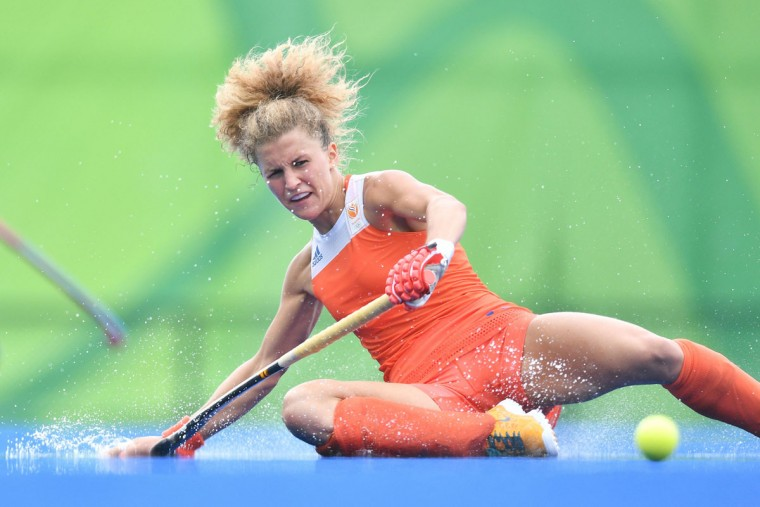 Netherlands' Maria Verschoor slips on the rain water during the womens's field hockey New Zealand vs Netherlands match of the Rio 2016 Olympics Games at the Olympic Hockey Centre in Rio de Janeiro on August, 12 2016. / (AFP Photo/Carl Souzacarl de souza)