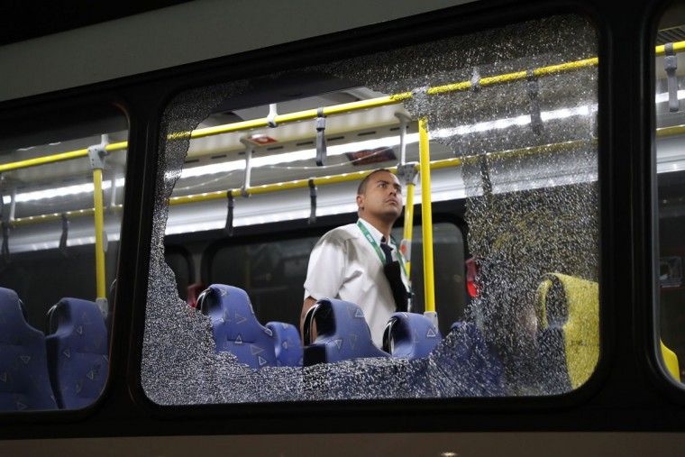 The damages to the windows of an Olympic journalists bus hit while driving on the transolympica highway are inspected by an official in Rio de Janeiro on August 9, 2016. (MAXIMILIANO AMENA/AFP/Getty Images)