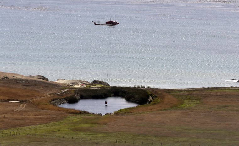 A helicopter picks up water in a pond on the edge of the El Sur Ranch as firefighters battle a wildfire in Big Sur on Thursday, Aug. 4, 2016. (David Royal/The Monterey County Herald via AP)