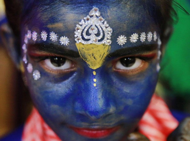 An Indian student who got her face painted with blue color looks at camera ahead of Janmashtami celebrations at a college in Mumbai, India, Tuesday, Aug. 23, 2016. Janmashtami, is an annual celebration of the birth of the Hindu deity Krishna. (AP Photo/Rafiq Maqbool)