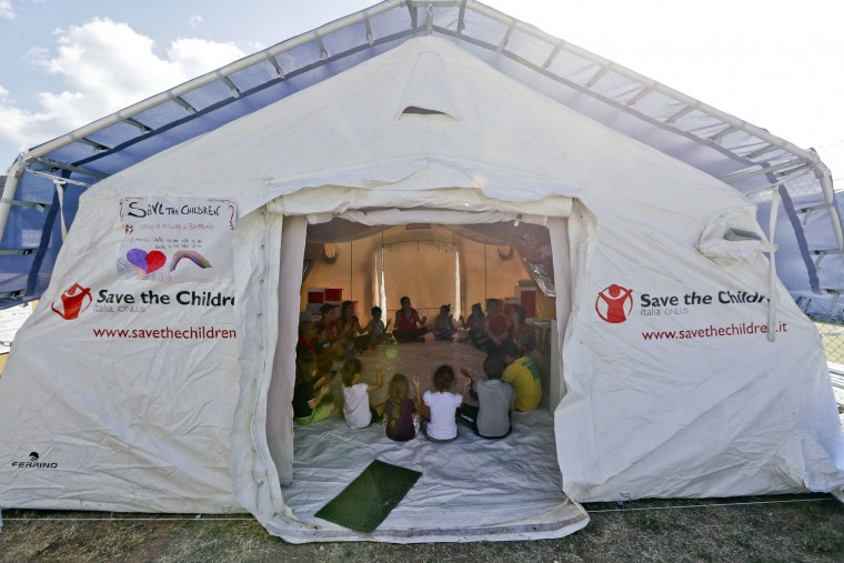 Children play in a tent set up for them by the 'Save the Children' humanitarian organization, in Amatrice, Friday, Aug. 26, 2016. Rescue crews have raced against time since a devastating earthquake leveled three towns in central Italy last Wednesday Aug. 23, leaving hundreds dead. (AP Photo/Andrew Medichini)