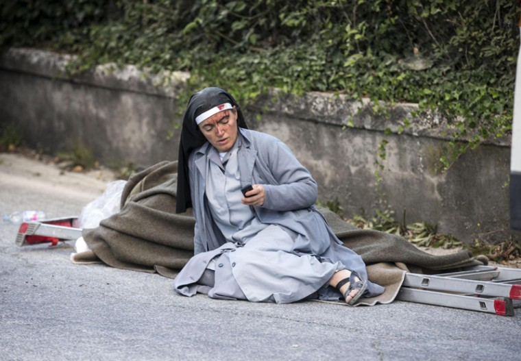 A nun checks her mobile phone as she lies near a ladder following an earthquake in Amatrice, Italy, on Wednesday. (Massimo Percossi/ANSA via AP)