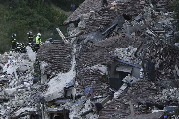 Rescuers search amid rubble following an earthquake in Pescara Del Tronto, Italy, on Wednesday. (Gregorio Borgia/AP)