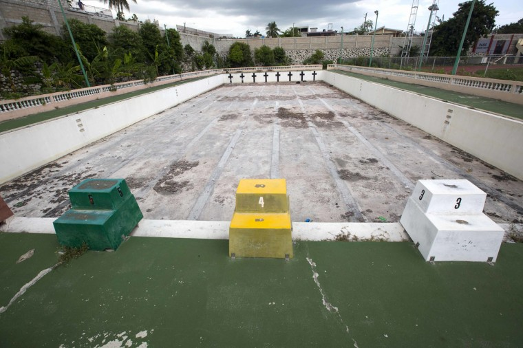 This July 30, 2016 photo, shows Haiti's only 50 meter swimming pool in the Port-au-Prince neighborhood Carrefour. The derelict Olympic size swimming pool has been out of commission since 1990. (AP Photo/Dieu Nalio Chery)