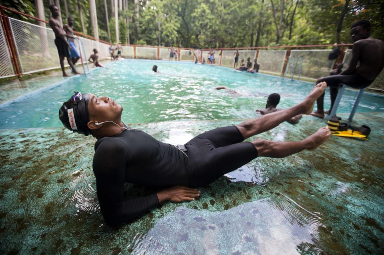 In this July 21, 2016 photo, Haitian Olympic swimmer Frantz Mike Itelord Dorsainvil stretches before swimming laps a private swimming pool, in the Port-au-Prince neighborhood Carrefour, Haiti. It's been nearly 90 years since Haiti earned a medal at the Olympic Games. But Dorsainvil is aiming to break that dry spell. (AP Photo/Dieu Nalio Chery)