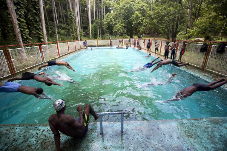 In this July 21, 2016 photo, teens dive into the pool during a lesson at a private pool in the Port-au-Prince neighborhood Carrefour, Haiti. Swimming barely exists as a sport in Haiti, where there are few pools. Many Haitians, even some who fish for a living, never learn how to swim. (AP Photo/Dieu Nalio Chery)