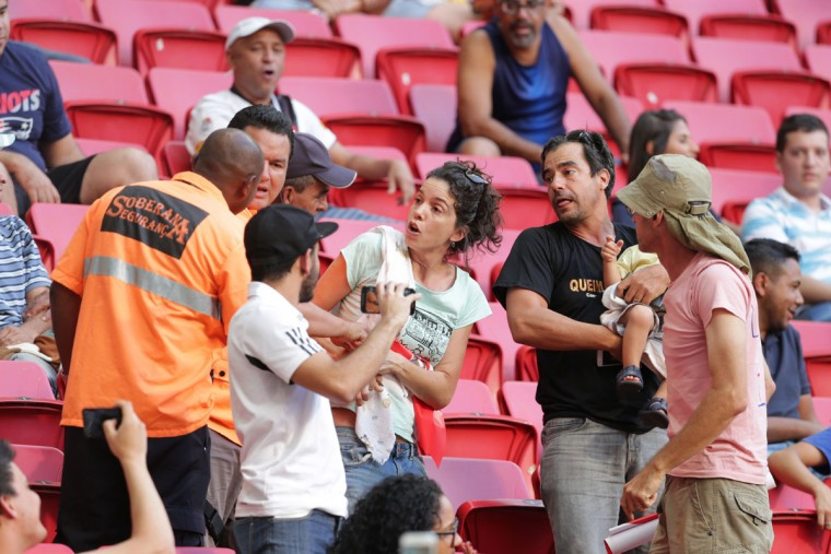 Security officers try to take from a woman away a sign against Brazil's interim Michel Temer during a F match of the women's Olympic football tournament between Germany and Canada at the National Stadium, in Brasilia, Brazil, Tuesday, Aug. 9, 2016. A Brazilian judge has order Olympic organizers to allow peaceful protests inside venues after several fans were escorted out of stadiums for holding up anti-government signs. (AP Photo/Eraldo Peres)