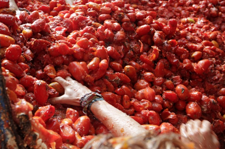 """A reveler takes tomatoes to throw into the crowd during the annual """"Tomatina"""" tomato fight festival in the village of Bunol, Spain. (Alberto Saiz/AP)"""