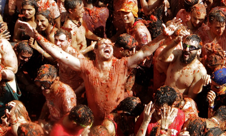 "Revelers throw tomatoes at each other during the annual ""Tomatina"" tomato fight festival in the village of Bunol, about 30 miles outside Valencia, Spain, on Wednesday. The streets of an eastern Spanish town are awash with red pulp as thousands of people pelt each other with tomatoes in the annual ""Tomatina"" battle that has become a major tourist attraction. At the annual fiesta in Bunol on Wednesday, trucks dumped 160 tons of tomatoes for some 20,000 participants, many from abroad, to throw during the hour-long morning festivities. (Alberto Saiz/AP)"