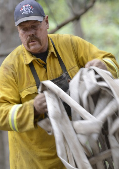 Red Bluff Fire strike team leader Ray Barber's face is covered with soil as he unloads large piles of hoses that were removed from Long Ridge near the Gate at Palo Colorado Canyon as firefighters battle a wildfire in Big Sur on Thursday, Aug. 4, 2016. Officials say more than two dozen large wildfires are burning in the West. Hot, windy weather has made conditions difficult for firefighters as the blazes destroy homes and force evacuations. (David Royal/The Monterey County Herald via AP)