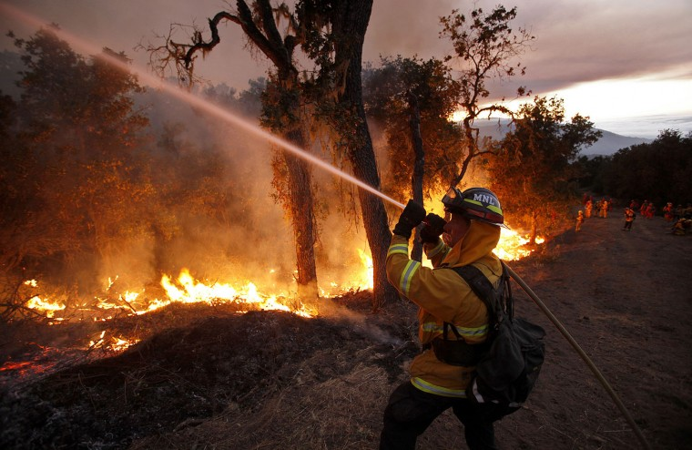 In this photo taken Tuesday, Aug. 2, 2016, Cal Fire crews conduct a firing operation west of Cachagua, Calif. A wildfire north of Big Sur near California's Central Coast has grown again overnight after burning for nearly two weeks. The fire has scorched more than 79 square miles and is less than 30 percent contained. It has destroyed 57 homes and is threatening another 2,000 structures. (Vern Fisher/Monterey Herald via AP)