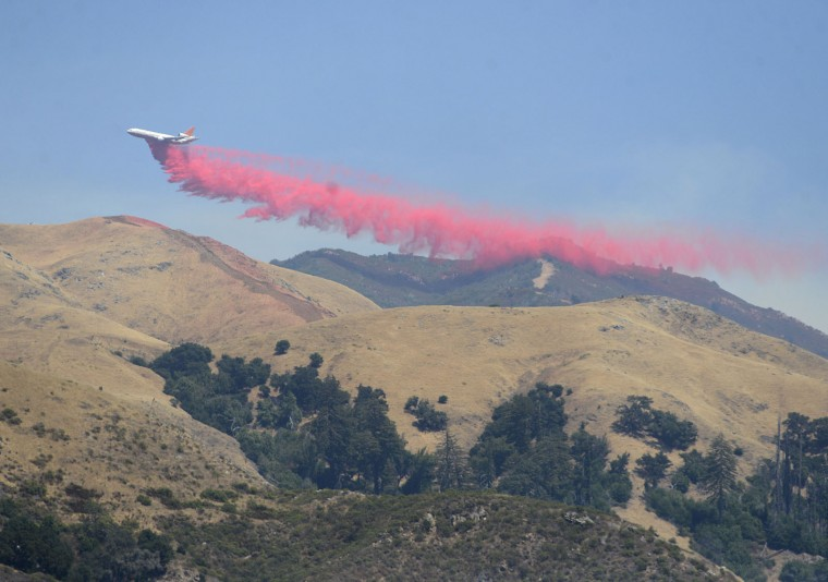 A very large tanker makes a fire retardant drop in the area of Post Summit and Manuel Peak east of the village of Big Sur, Calif., as firefighters battle a wildfire on Thursday, Aug. 4, 2016. Officials say more than two dozen large wildfires are burning in the West on Thursday. A stubborn wildfire north of Big Sur near California's Central Coast has grown after burning for nearly two weeks in steep, forested ridges. (David Royal/The Monterey County Herald via AP)