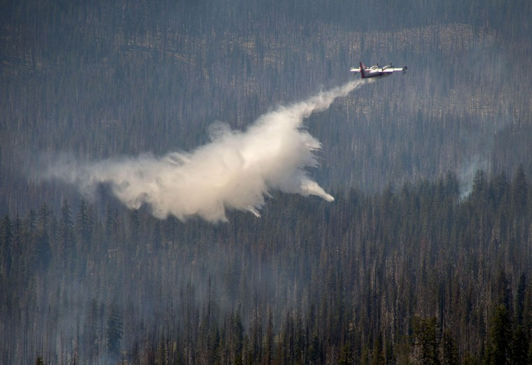 A firefighting aircraft helps battle a wildfire southwest of Crater Lake, Ore., Thursday, Aug. 4, 2016. A wildfire burning southwest of Crater Lake prompted an evacuation warning for some parts of Crater Lake National Park. (Brian Davies/The Register-Guard via AP)