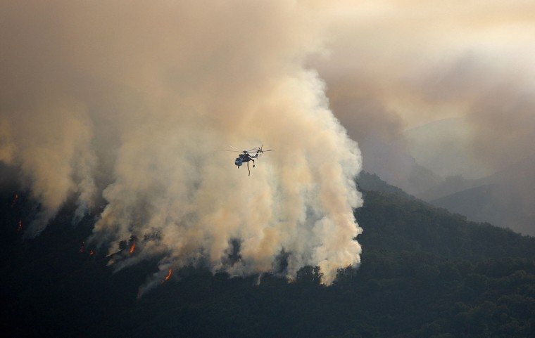 In this photo taken Tuesday, Aug. 2, 2016, a Sikorsky helitanker works the Soberanes Firewest of Cachagua, Calif. A wildfire north of Big Sur near California's Central Coast has grown again overnight after burning for nearly two weeks. The fire has scorched more than 79 square miles and is less than 30 percent contained. It has destroyed 57 homes and is threatening another 2,000 structures. (Vern Fisher/Monterey Herald via AP)