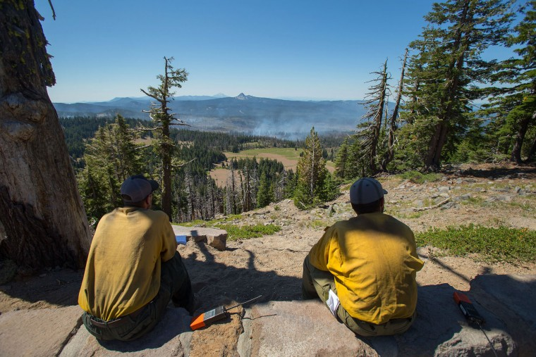 Firefighters watch the progress of a wildfire southwest of Crater Lake, Ore., from the rim of the crater Thursday, Aug. 4, 2016. A wildfire burning southwest of Crater Lake prompted an evacuation warning for some parts of Crater Lake National Park. (Brian Davies/The Register-Guard via AP)