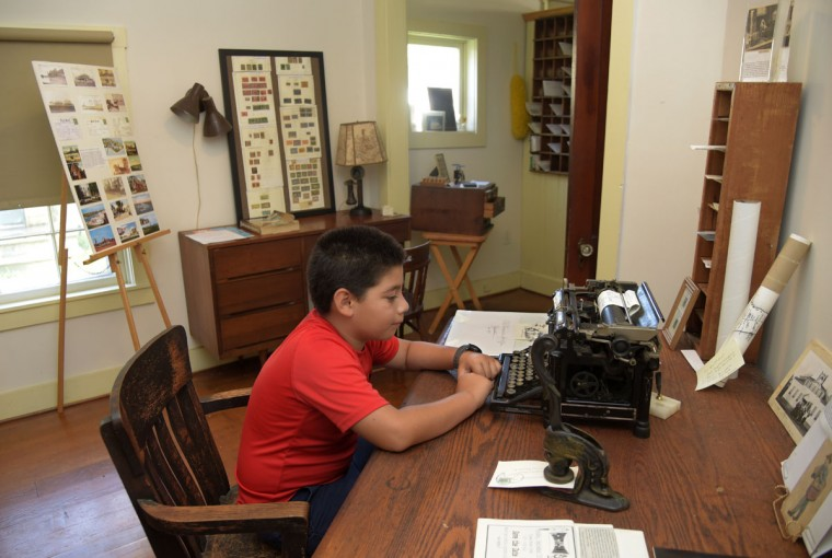 "George Cook, grandson to Nancy Cook, chair of the Historic Stevensville Arts & Entertainment District, examines an old typewriter in the historic post office in Stevensville, Md. According to the Kent Island Heritage Society, Inc.: ""The government paid rent of $18.75 a month and the outlandish sum of $25 a year to heat the structure."" The building date is unknown but it is pictured on an 1877 map. (Algerina Perna/Baltimore Sun)"