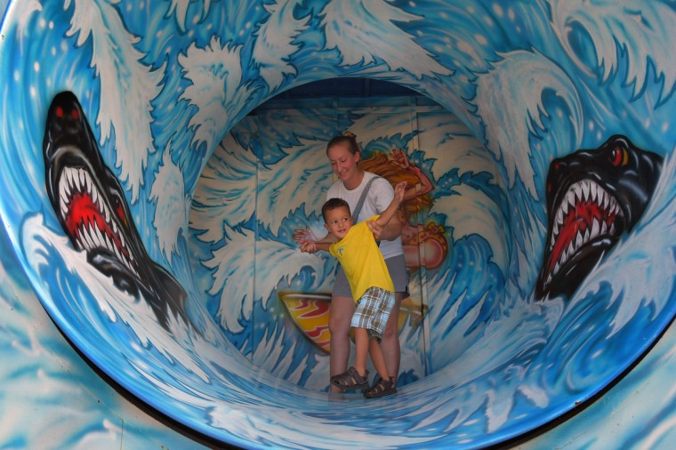 Navigating the final part of a funhouse, Kelsey Raffaeli of Abingdon stands behind her son Brian Bromell Jr., 3, who shows caution entering the barrel of fun, during the annual Harford County Farm Fair. (Karl Merton Ferron / Baltimore Sun)