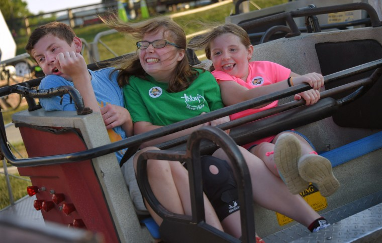 From left, siblings Mark Hopkins, 14, Emily Hopkins, 15, and Katie Hopkins, 10 of Bel Air show varying results of the crush of centrifugal force while being whipped around on the Sizzler, during the annual Harford County Farm Fair. (Karl Merton Ferron / Baltimore Sun)