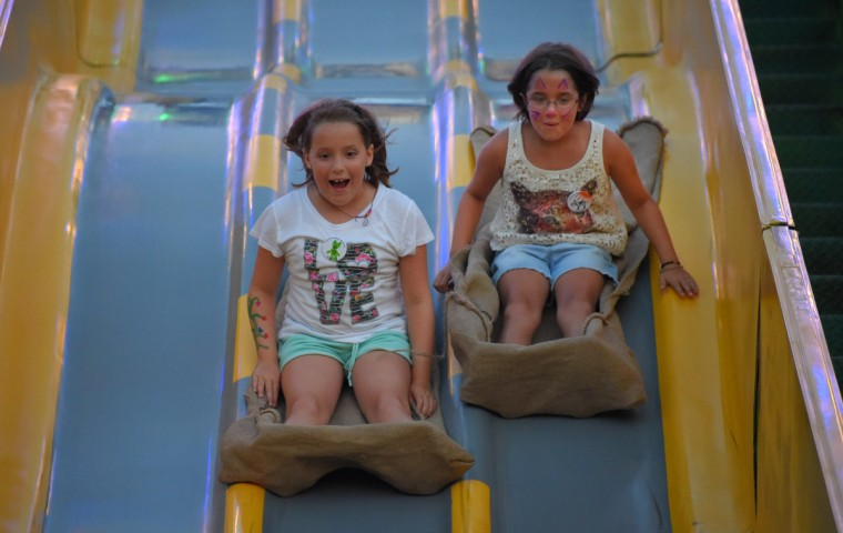 Nine-year-old twin sisters Addyson Phoebus (left) and Maya Phoebus of Delta, PA race down the slide during the annual Harford County Farm Fair. (Karl Merton Ferron / Baltimore Sun)
