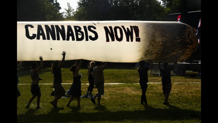Protesters in favor of marijuana legalization carry an inflatable joint at FDR Field near the Wells Fargo Arena on June 27.