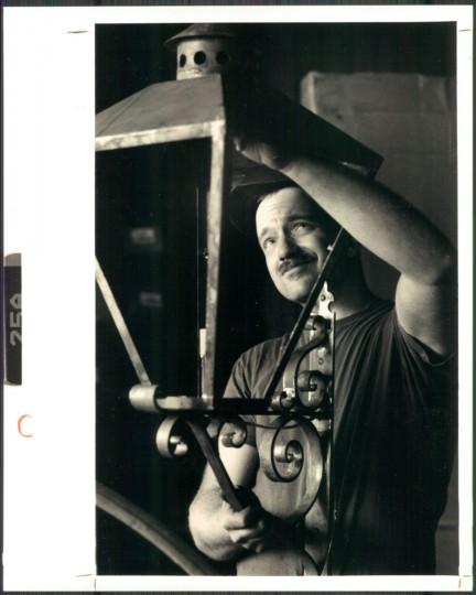 Clay Miller checks fitting on a lamp fixture. October 14, 1989. (Kirschbaum/Baltimore Sun)