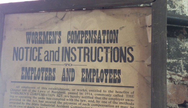 "An antique sign advises workers at G. Krug & Son of their entitlement to workmen's compensation. ""As a blacksmith, you have to expect that you will get burned at some point,"" says Manar. ""It's a matter of learning how to avoid it."" (Christina Tkacik/Baltimore Sun)"
