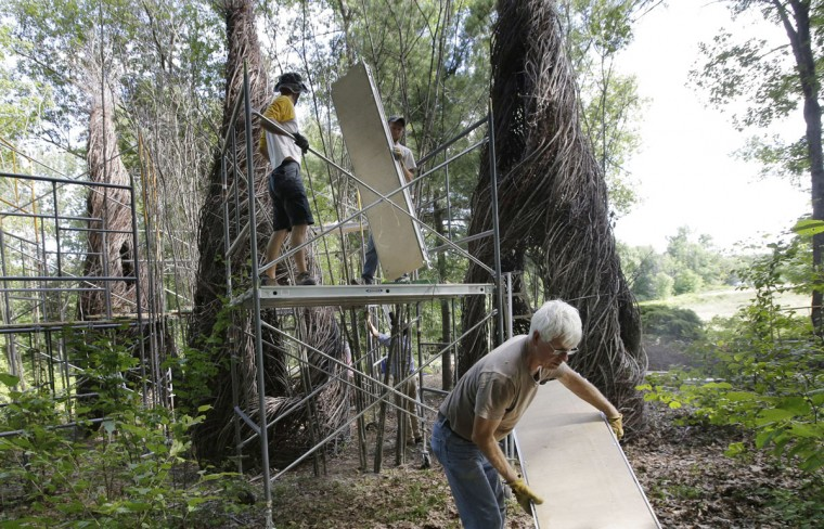 "In this Wednesday, Aug. 17, 2016, photo, sculptor Patrick Dougherty, front, carries a piece of scaffolding while constructing a sculptural installation ""The Wild Rumpus,"" from branches and sticks on the grounds of the Tower Hill Botanic Garden, in Boylston, Mass. Dougherty's installation opens to the public Thursday, Aug. 25. (AP Photo/Steven Senne)"
