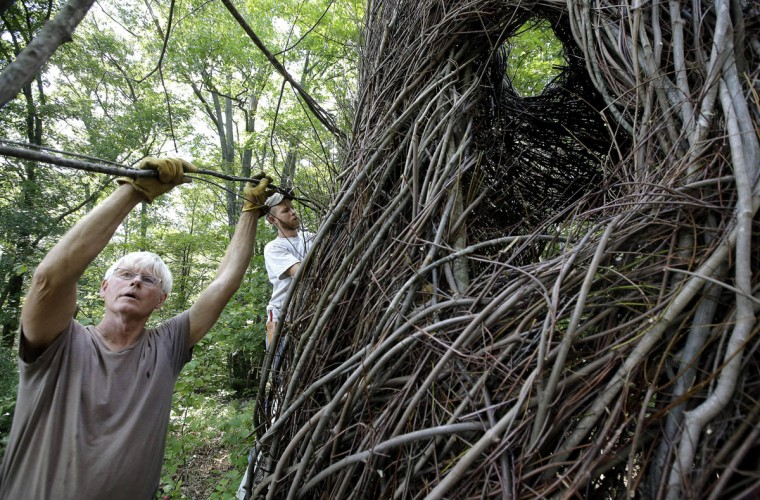 "In this Wednesday, Aug. 17, 2016 photo sculptor Patrick Dougherty, left, works with his son and assistant Sam Dougherty, behind, as they construct a sculptural installation ""The Wild Rumpus,"" from branches and sticks on the grounds of the Tower Hill Botanic Garden, in Boylston, Mass. Dougherty's installation opens to the public Thursday, Aug. 25, at Tower Hill Botanic Garden. (AP Photo/Steven Senne)"