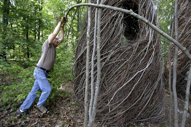 "In this Wednesday, Aug. 17, 2016 photo sculptor Patrick Dougherty, left, bends a sapling while constructing a sculptural installation ""The Wild Rumpus,"" from branches and sticks on the grounds of the Tower Hill Botanic Garden, in Boylston, Mass. Dougherty's installation opens to the public Thursday, Aug. 25. (AP Photo/Steven Senne)"