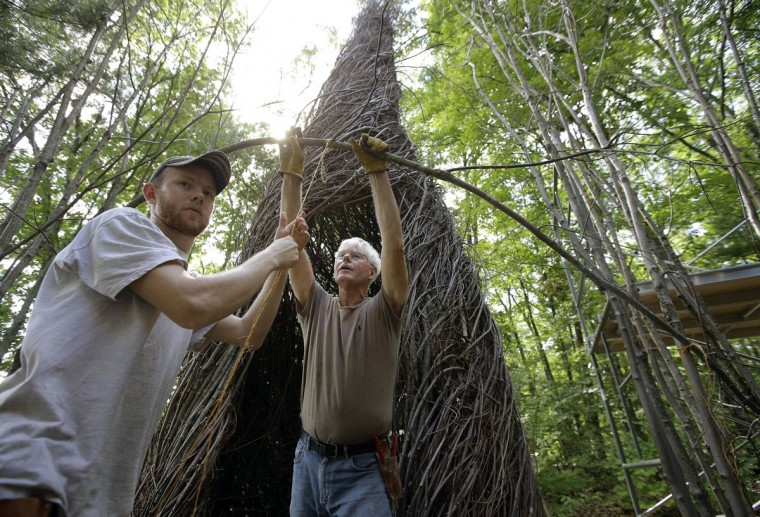 "In this Wednesday, Aug. 17, 2016 photo sculptor Patrick Dougherty, center, works with his son and assistant Sam Dougherty, left, as they construct a sculptural installation ""The Wild Rumpus,"" from branches and sticks on the grounds of the Tower Hill Botanic Garden, in Boylston, Mass. Dougherty's installation opens to the public Thursday, Aug. 25. (AP Photo/Steven Senne)"