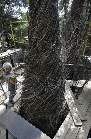 "In this Wednesday, Aug. 17, 2016 photo sculptor Patrick Dougherty, left, works to construct a sculptural installation ""The Wild Rumpus,"" from branches and sticks on the grounds of the Tower Hill Botanic Garden, in Boylston, Mass. Dougherty's installation opens to the public Thursday, Aug. 25. (AP Photo/Steven Senne)"