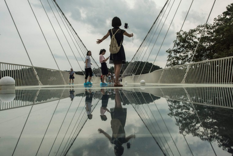 A tourist takes a photograph on the world's highest and longest glass-bottomed bridge above a valley in Zhangjiajie in China's Hunan Province on August 20, 2016. (FRED DUFOUR/AFP/Getty Images)