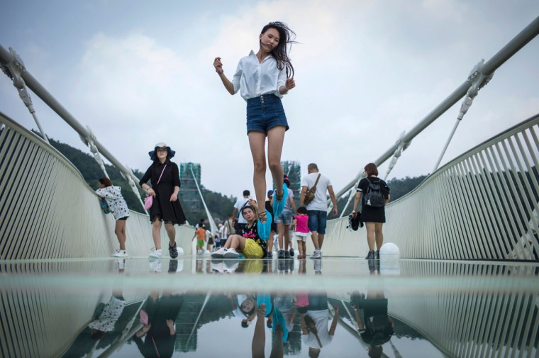 A visitor jumps for a photograph on the world's highest and longest glass-bottomed bridge above a valley in Zhangjiajie in China's Hunan Province on August 21, 2016. (FRED DUFOUR/AFP/Getty Images)