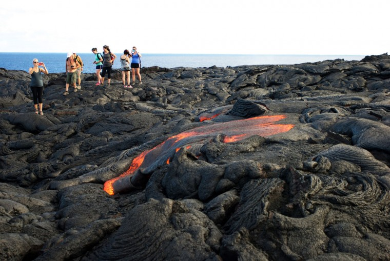 In this Monday, Aug. 8, 2016 photo, visitors look at lava from Kilauea, an active volcano on Hawaii's Big Island, as it flows toward the ocean in Volcanoes National Park near Kalapana, Hawaii. The current lava flow erupted from a vent on the volcano in May and made its way to the sea in late July. Visitors can hike about 10 miles round trip to see the lava, or take a boat or helicopter tour to see the flow. (AP Photo/Caleb Jones)