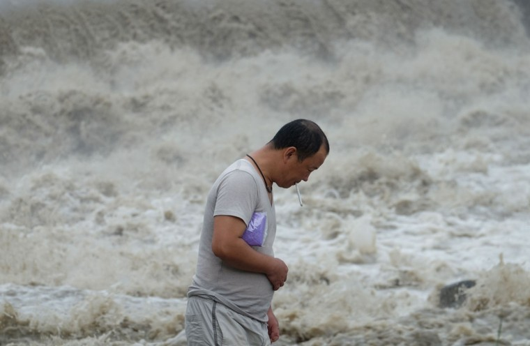 A local resident smokes next to the Xindian river in the aftermath of typhoon Megi at Xindian district in New Taipei City on September 28, 2016. Typhoon Megi hit the Chinese mainland early in the morning on September 28 killing one, after leaving a trail of destruction in Taiwan, where four are dead and a million still without power. (SAM YEH/AFP/Getty Images)