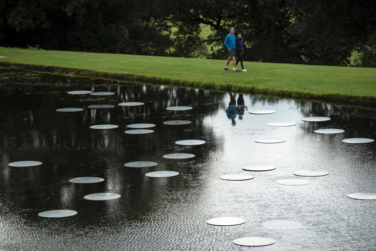 Members of the public walk past sculptures by British artist Bruce Munro entitled 'Time and Again' that feature in the 'Beyond Limits' exhibition in the grounds of Chatsworth House near Bakewell, northern England, on September 9, 2016. (OLI SCARFF/AFP/Getty Images)