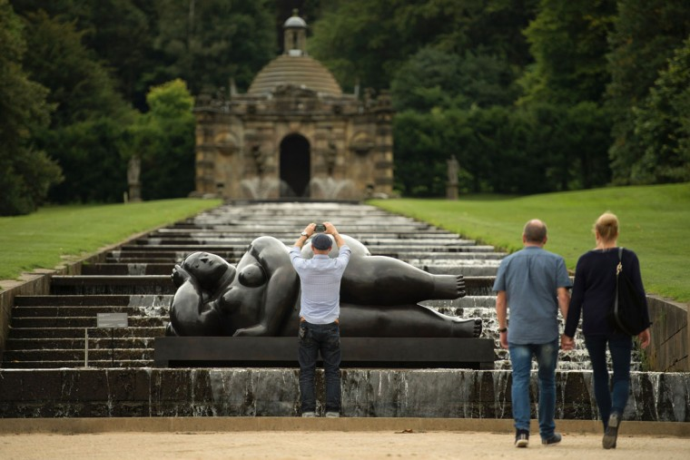 A man photographs a sculpture by Colombian artist Fernando Botero entitled 'Donna Sdraiata' that features in the 'Beyond Limits' exhibition in the grounds of Chatsworth House near Bakewell, northern England, on September 9, 2016. (OLI SCARFF/AFP/Getty Images)